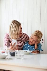 mor og sønn ved kjøkkenbord