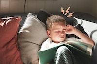 Gutt leser på sofa