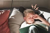 Gutt sofa leser hodepine