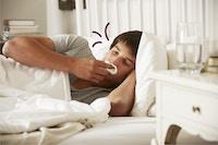 Ung mand i sengen med influenza
