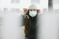 Kvinde med hat og ansigtsmaske