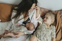 Mor i seng med barn ammer
